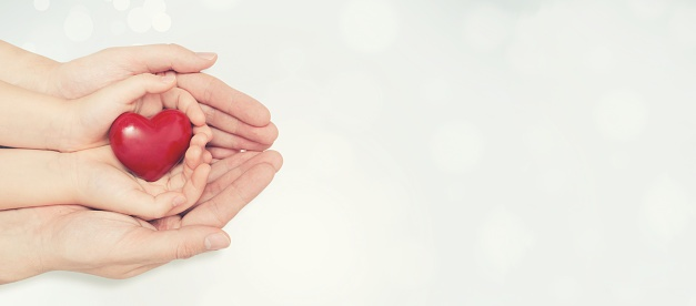 Parent Who Received Family Planning Services Holding Child's Hand Holding a Heart