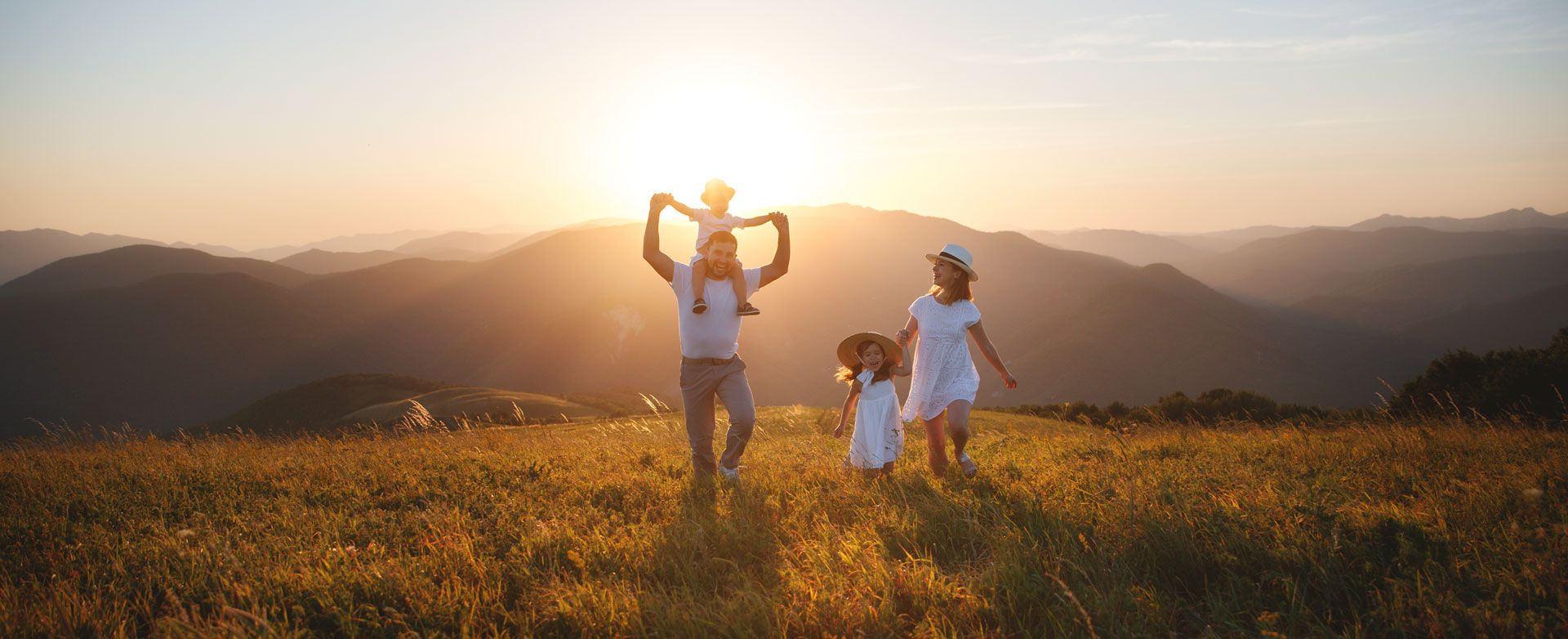 Family hiking in a field with mountains